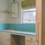 13 of 15 photographs. Another bathroom is shown, this one in mainly aqua and green colors. The edge of a wall has a vertical grip rail, and the walls and cabinets show atmospheric deterioration.