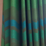6 of 15 photographs. A close-up view of the folds of fabric of the curtain. The fabric is in shades of green and teal, with horizontal stripes of each color. These stripes emphasize the wave of the curtain's folds.