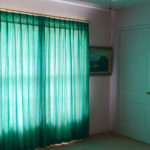 10 of 15 photographs. In another room, a dark room with lilac walls is lit by sunlight through a green curtain. The mixing of these colors gives a strange, beautiful character to the room.