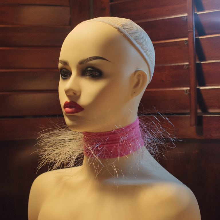A photograph documenting the artwork Throat Apparatus. The apparatus is a piece of pink, elastic fabric with hundreds of clear monofilament threads emerging from it like hair. This strip is worn tight as a collar, giving the effect of a cloud of hairs around the neck. It is pictured here on a mannequin.